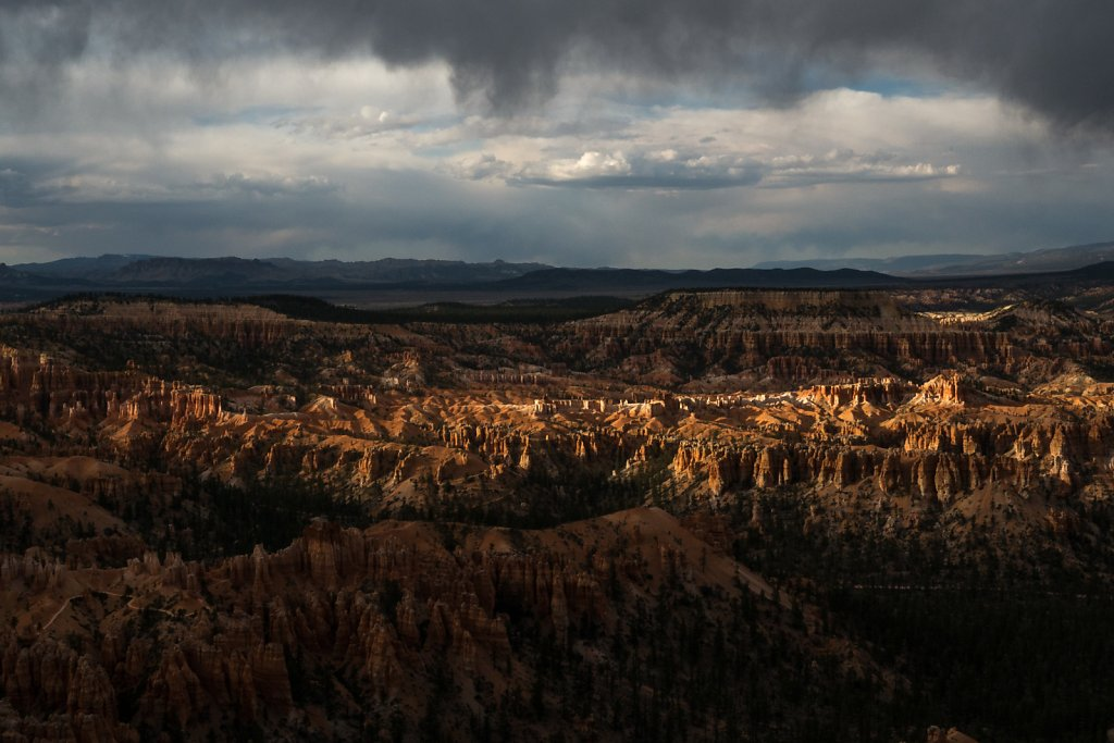 The last bit of sun pokes under the clouds to spotlight some of the hoodoos